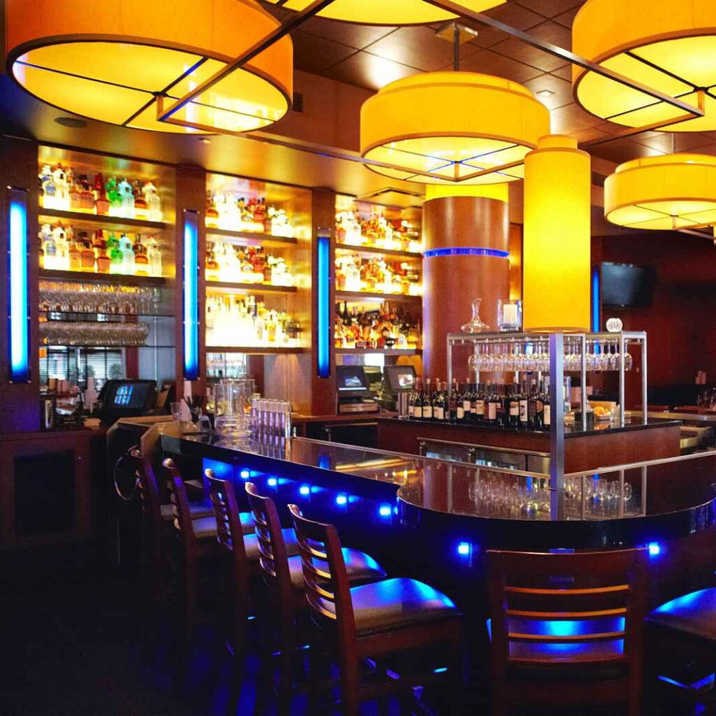 Horseshoe shaped bar lit by warm yellow chandeliers and blue neon accent lighting.