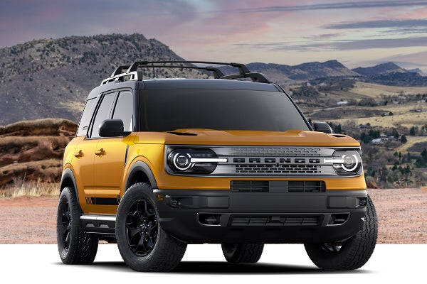 Yellow Ford SUV with mountains in background.