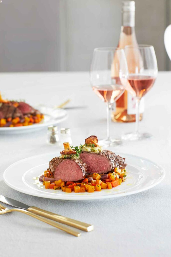 Beef cut on a bed of orange vegetables, white plate, and tablecloth. Glasses of rose wine behind table setting.