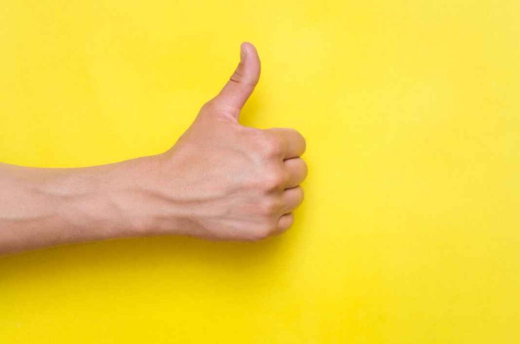 Man's hand giving thumbs up gesture against yellow background.