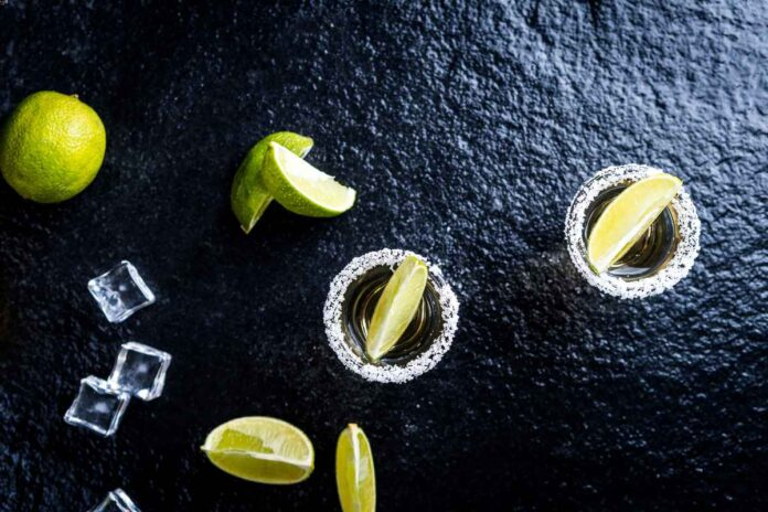 Flatlay of ice cubes, whole limes and lime wedges, and shot glasses with salted rims on black background.