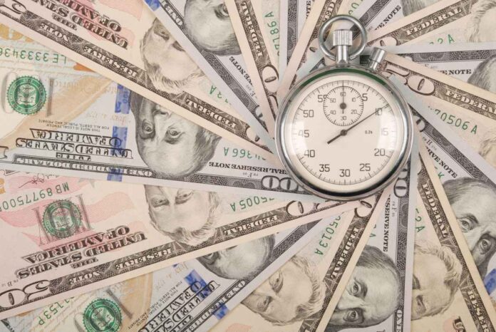 Stopwatch atop a spiral of US $50 and $100 bills.