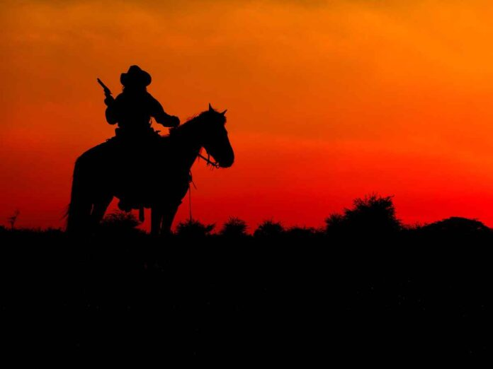 Silhouette of cowboy on horseback wearing a cowboy hat and brandishing a pistol against a red and orange sunset.