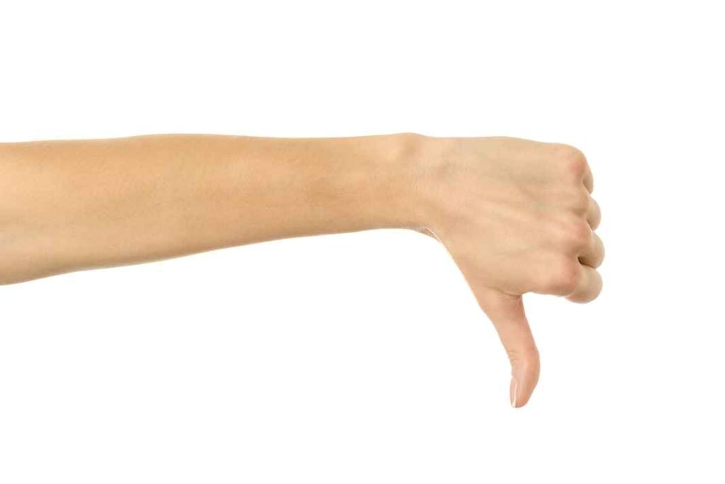 Woman's hand giving thumbs down gesture against white background.