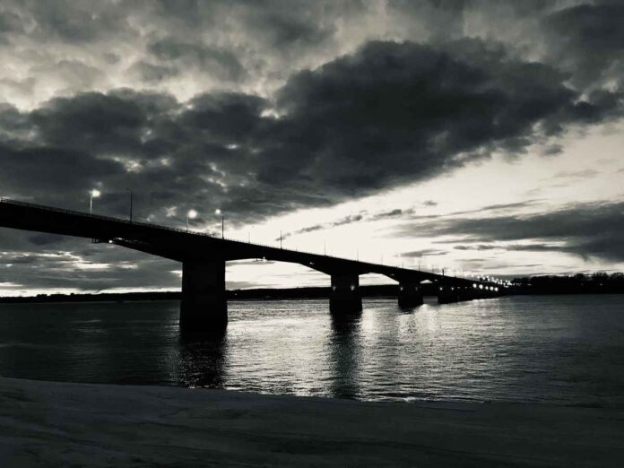 Black and white photo of bridge spanning wide river with dark clouds overhead.