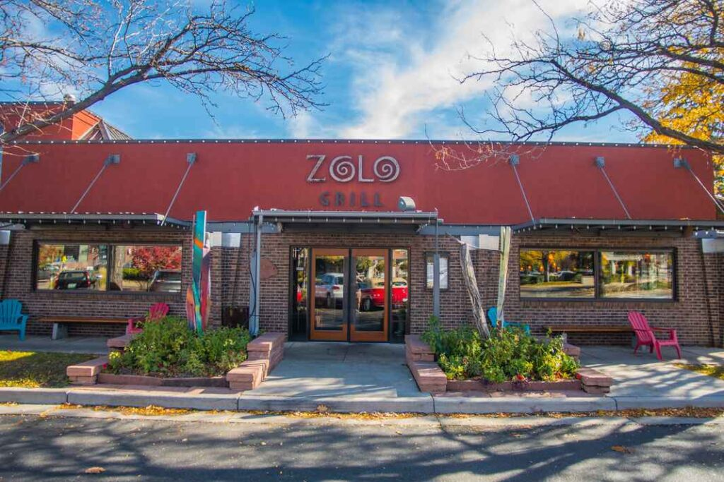 Brick exterior of Zolo Grill restaurant with blue skies in background.