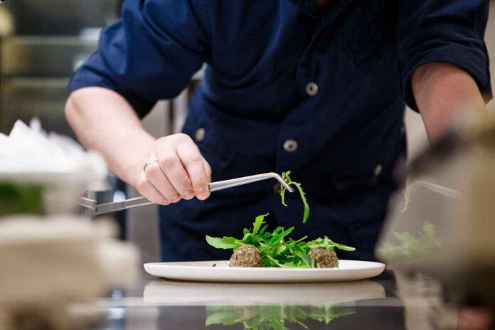Torso of chef wearing navy cook's jacket, holding tweezers to plate greens.