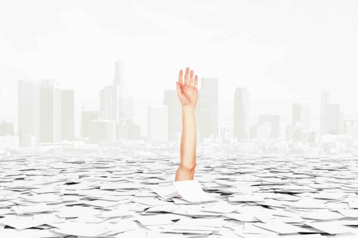 Human hand and arm rising out of an ocean of white paperwork against a city background.