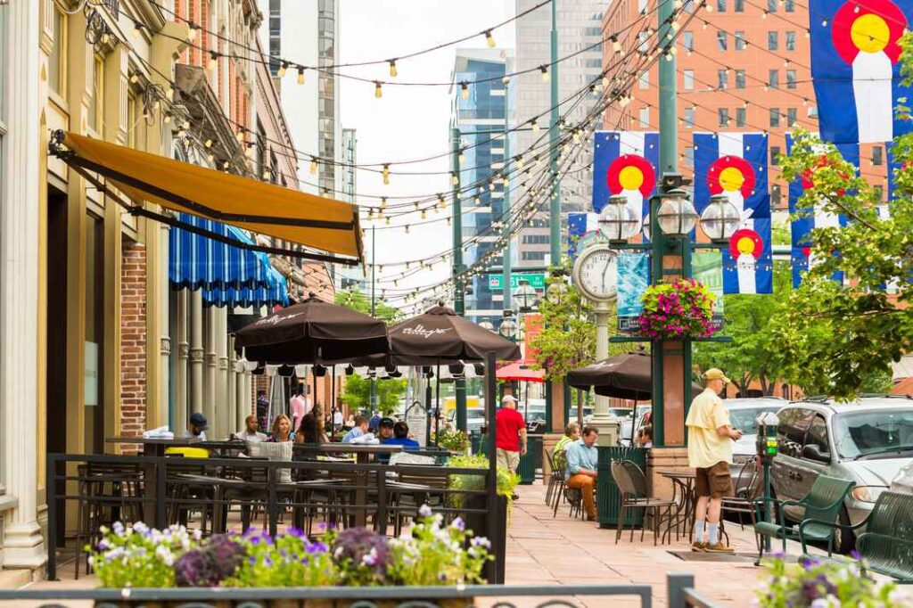 View of busy Larimer Street with restaurant patio tables under umbrellas, blue and white awnings, pedestrians, and Colorado flags hung over the street.