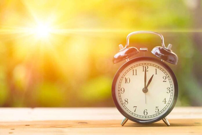 Retro alarm clock reading 1 o'clock on wooden bench with sun flare and blurry background.