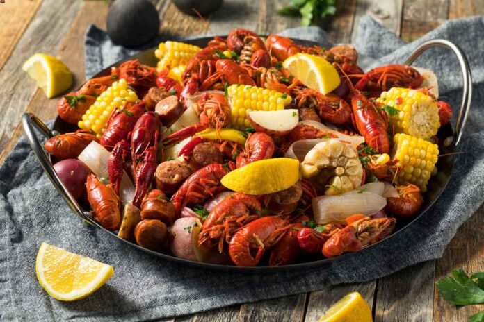 Homemade Southern crawfish boil with bright red crawfish, potatoes, sausage and bright yellow corn on a wooden table .