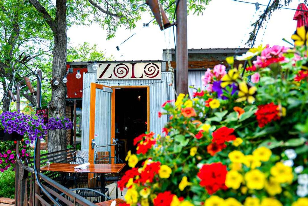 Entrance to Zolo patio with corrugated metal siding on building and patio tables surrounded by multicolored flowers and trees.