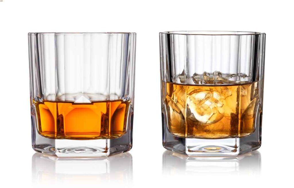 Two highball glasses of whiskey next to each other, one neat and one on the rocks.