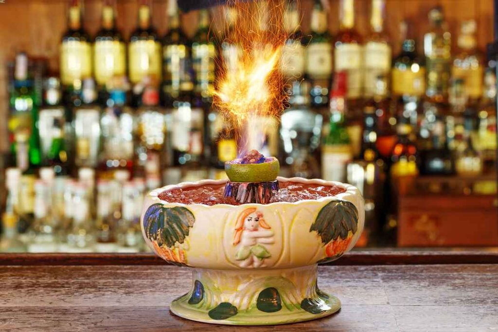 Ceramic scorpion bowl filled with boozy punch and with half a lime on fire. Out-of-focus backbar in background.