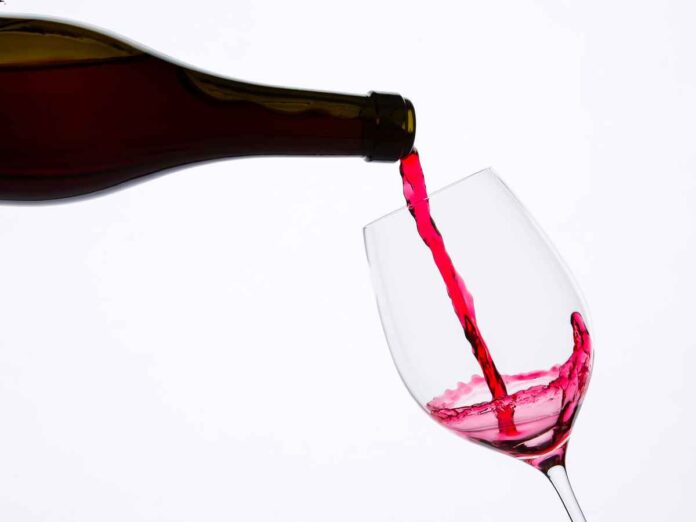 Bottle of red wine being poured into a stemmed wine glass.