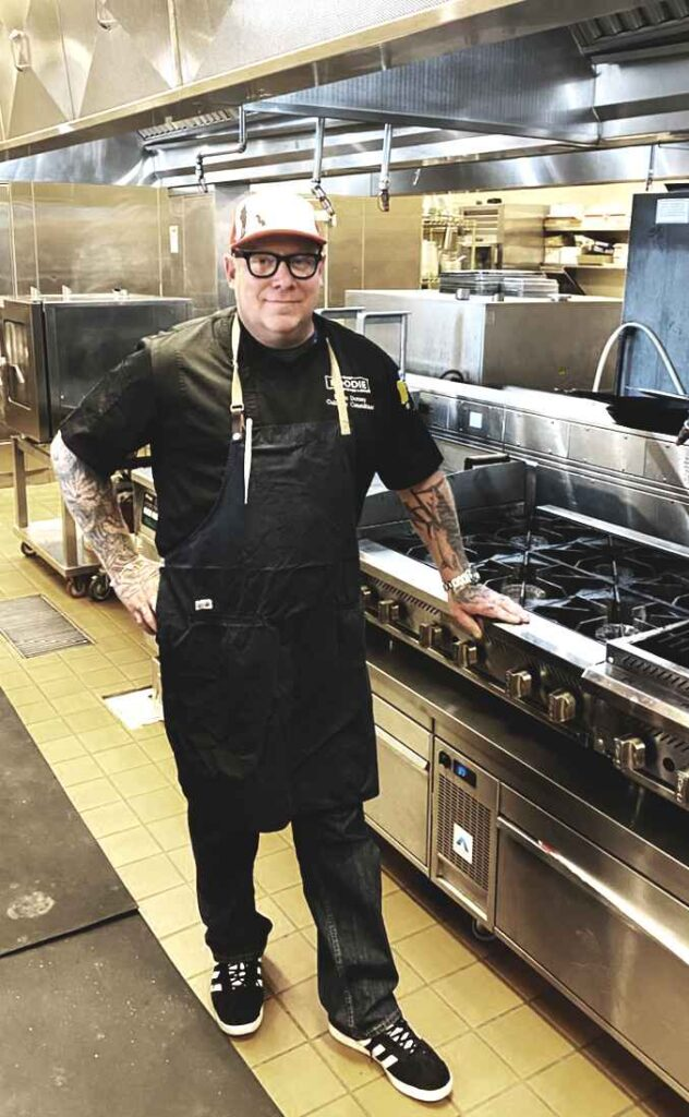 White chef with arm tattoos, glasses, and dressed in all black stands in a commercial test kitchen.