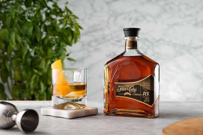 Bottle of Flor de Caña 18-Year rum on a white marble tabletop next to rocks glass with rum, a large ice cube, and orange peel inside. White marble and green foliage background.