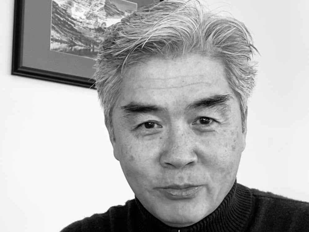 Black and white photo of Asian man with gray hair wearing a black zip-neck sweater.