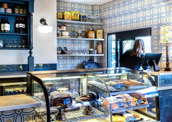 Restaurant interior with blue, yellow and white tiles, pastry case, and a blonde woman leaning out of a takeout window.