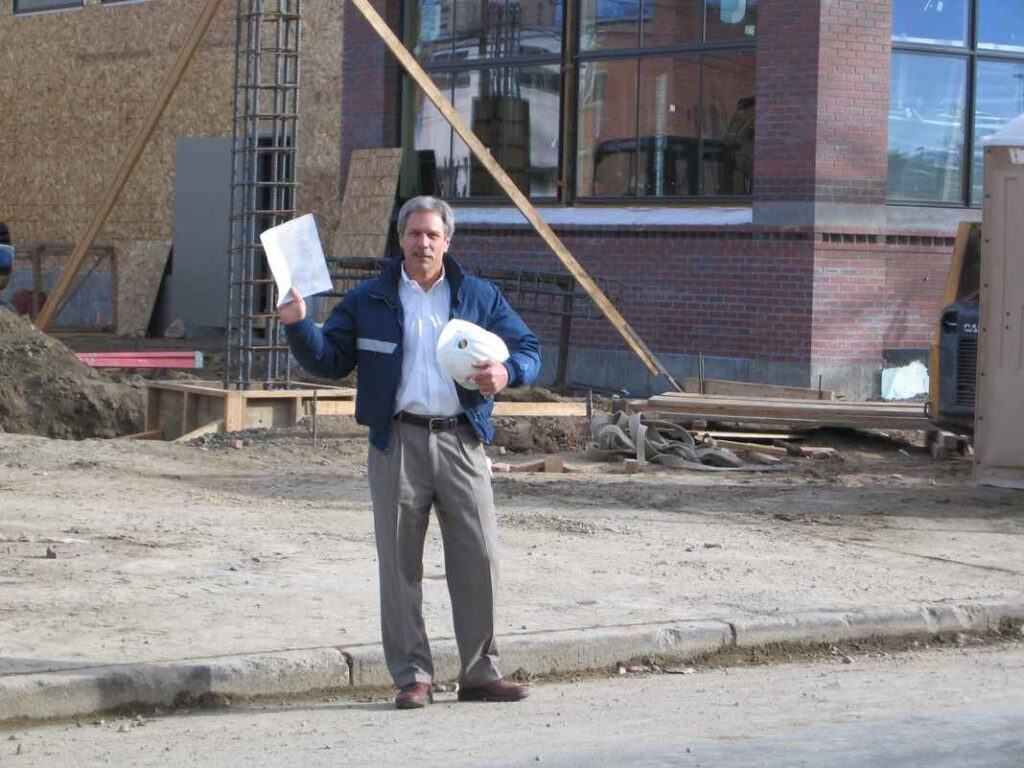 Middle aged man standing at construction site holding paperwork and a hard hat.