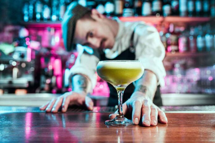 Male bartender with mustache and wearing a hat pushing a disgusting looking green cocktail across the bar.