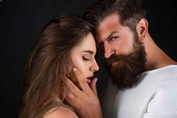 Bearded man and brunette woman standing close together while he touches her face and gives a sexy look to the camera. Black background.