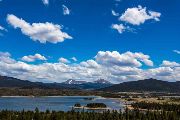 Large, blue lake surrounded by dark green evergreen trees, tall mountains in the background, and bright blue sky with white clouds.