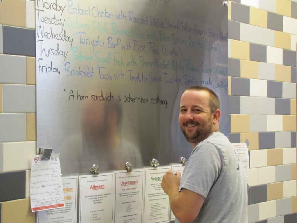 """Smiling man with beard looking over his shoulder. He is writing on a menu board, """"A ham sandwich is better than nothing."""""""