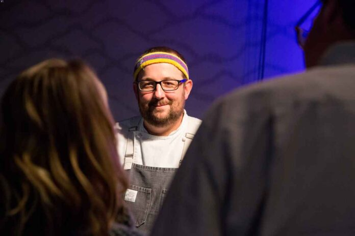 Smiling white man with beard and glasses wearing an apron and a sweatband on his head.