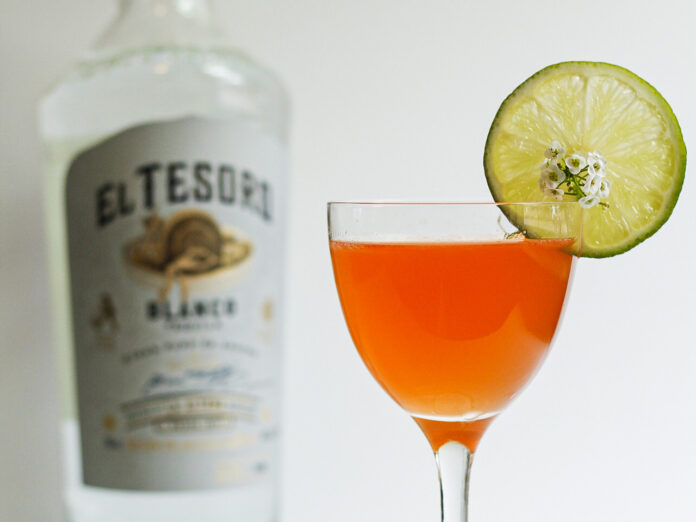 Amber cocktail in a stemmed glass garnished with dried lime wedge and tiny white flowers. Out of focus tequila bottle labeled El Tesoro in background.