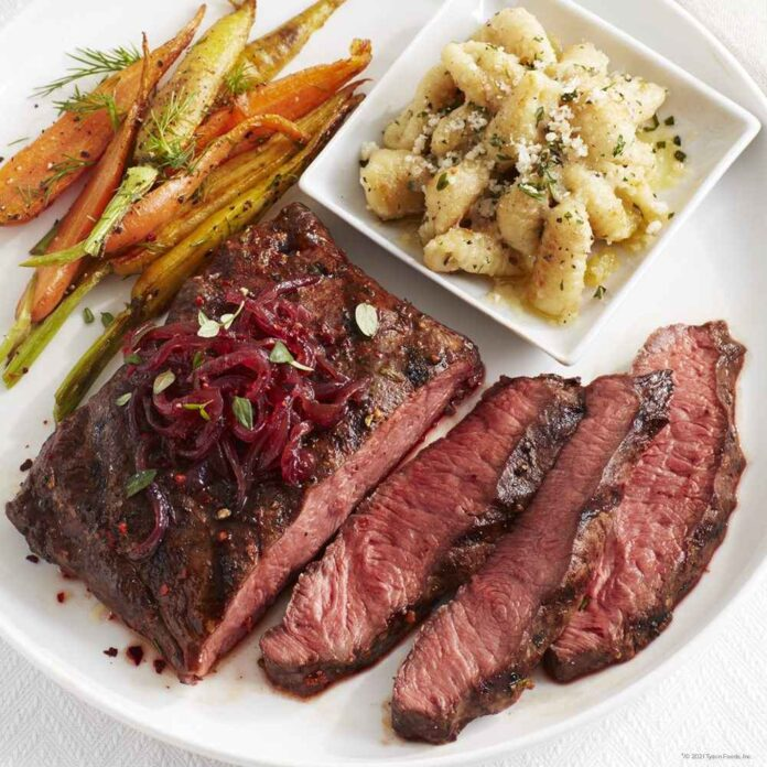 Roasted carrots, a pasta side dish, and cut of steak with three slices cut on a white plate.