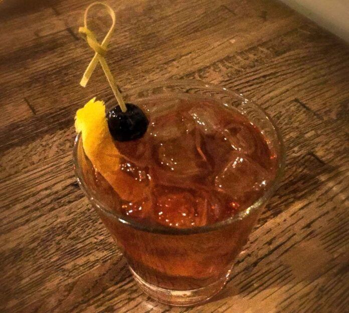 Close up of old fashioned glass filled with one large ice cube, orange peel and amber cocktail, garnished with a cherry on a skewer.