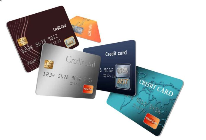 Five different credit cards in different colors scattered across a white background.