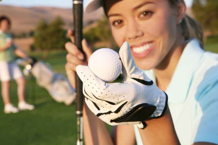 Smiling brunette woman wearing golf gear on the course and holding a golf club in one hand and golf ball in the other.