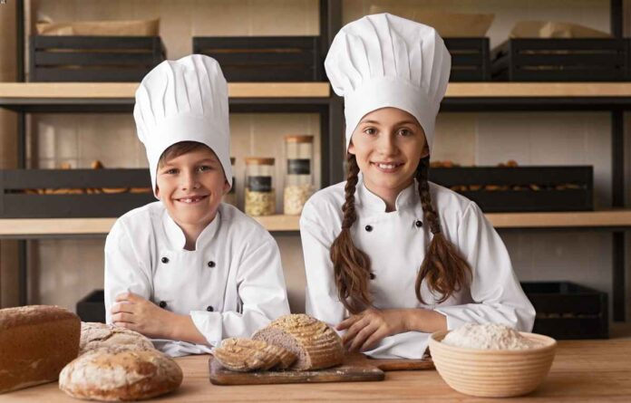 A young teenage boy and girl wearing white chefs coats and hats standing at a counter in front of loaves of fresh baked bread.