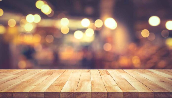 Wood texture table top with blurry gold lights in restaurant