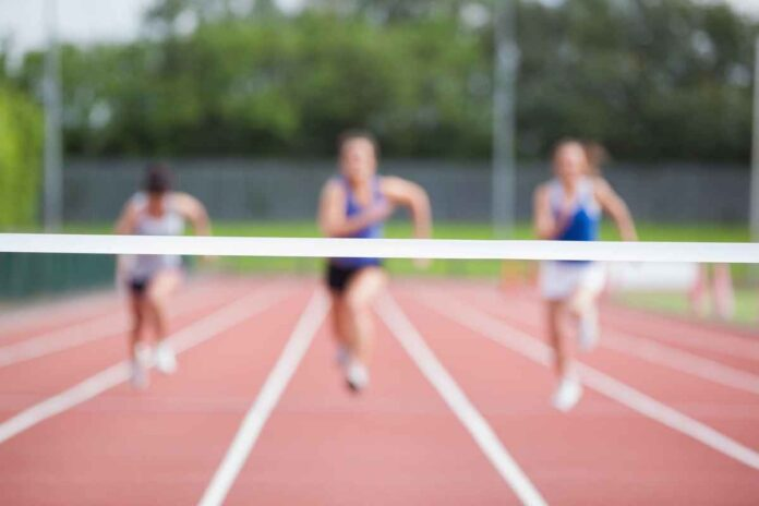 Three out-of-focus athletes running on a track towards a finish line. Finish line in focus.