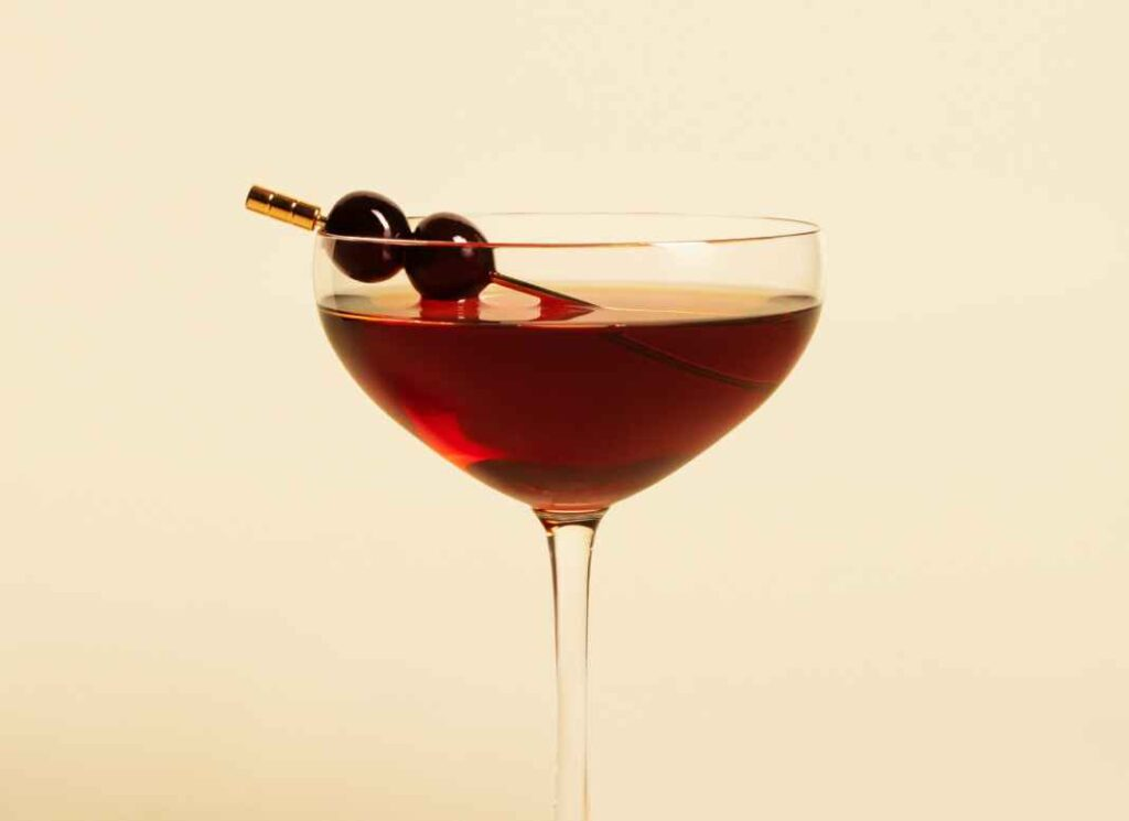 Dark red cocktail in stemmed glass garnished with two dark red cherries against pale yellow background.
