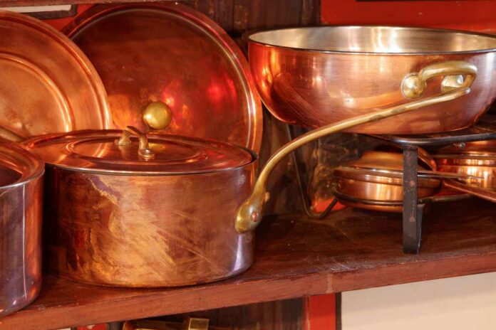 Shiny copper pots with lids on a wooden shelf in a kitchen.