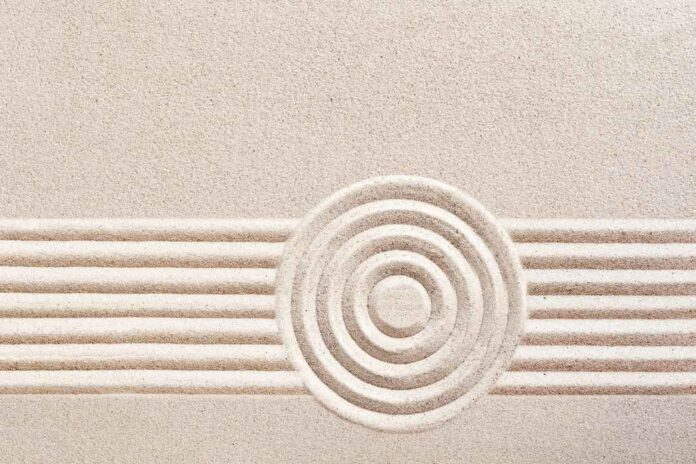 Very light tan sand with spiral indentation and horizontal vertical lines behind the spiral.