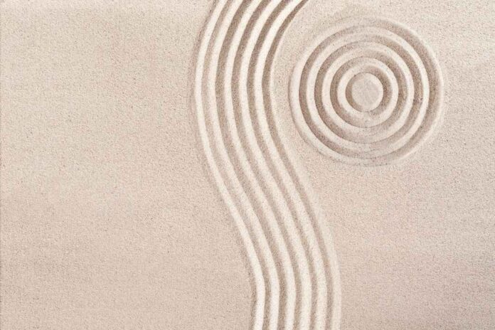 Light tan sand with bulls-eye indentation and wave vertical lines to the right of the bulls eye.