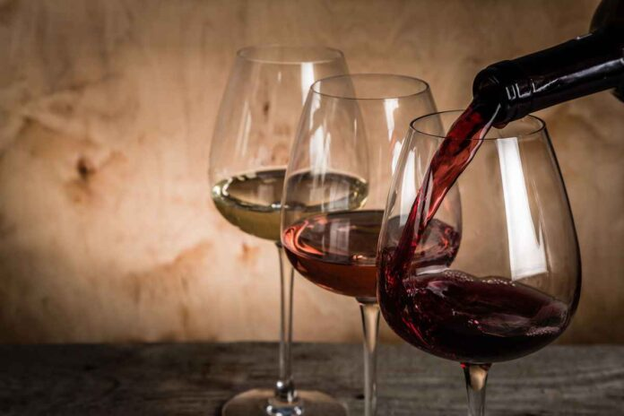 Three wine glasses offset against rustic tan background. One filled with white wine, one filled with rose wine and one with red wine being poured into it.