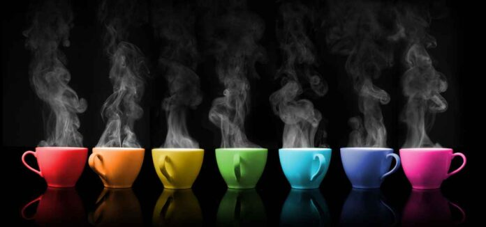 Seven steaming coffee cups against black background. Cups lined up in rainbow order.