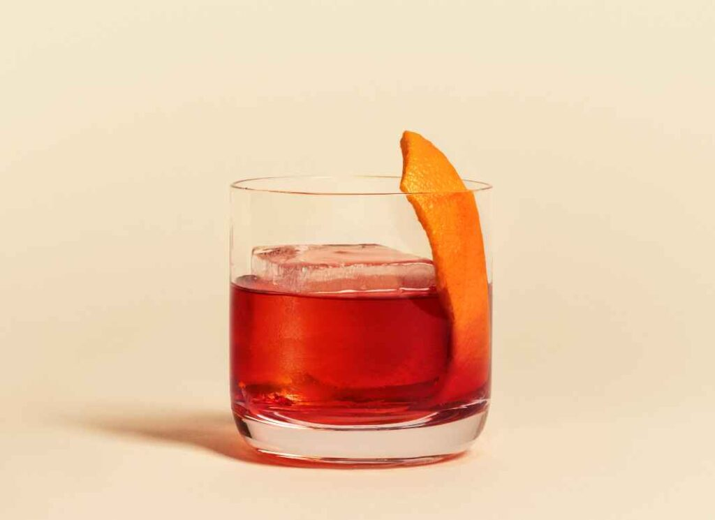 Bright red cocktail in rocks glass garnished with orange peel against pale yellow background.