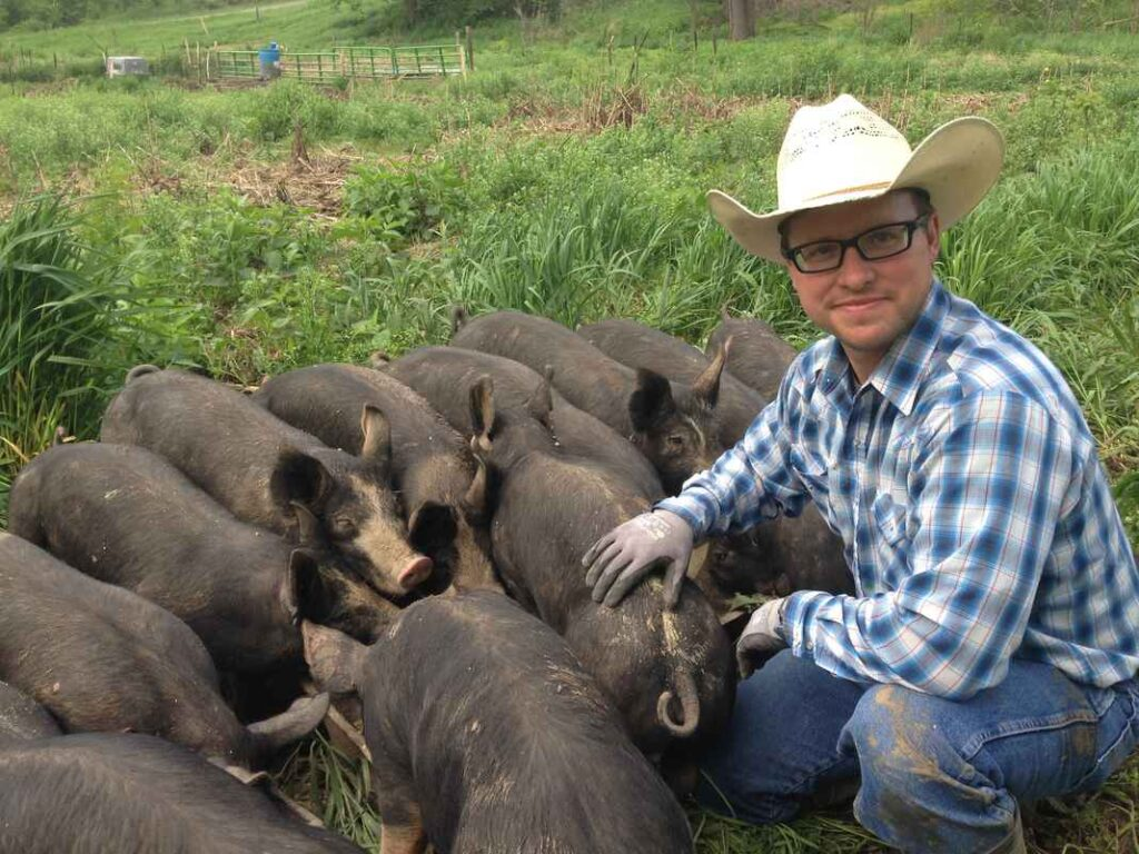 Man wearing glasses, cowboy hat and checked blue shirt crouched in a field with a herd of dark grey pigs.