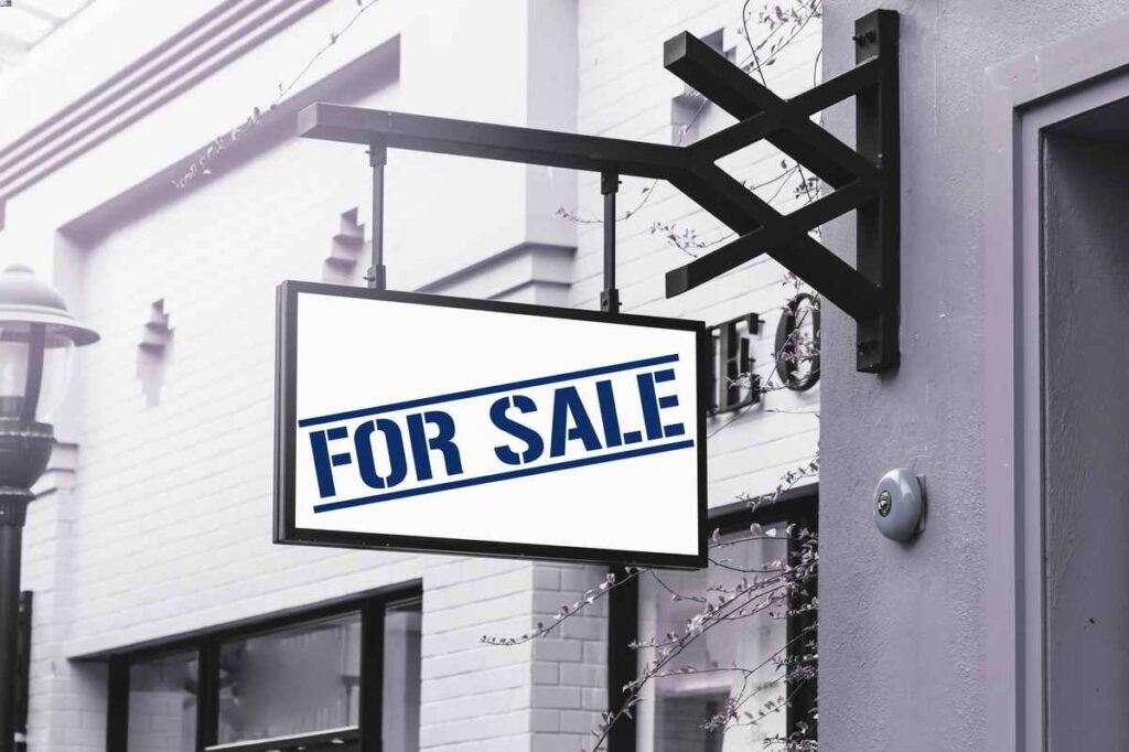 """Blue and white sign reading """"For Sale"""" on a commercial space with medium gray stucco and white brick walls."""