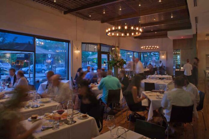 Restaurant dining room with blurry servers and customers moving around. Low lighting, white tablecloths and wine glasses on tables. Windows look out onto busy street at dusk.