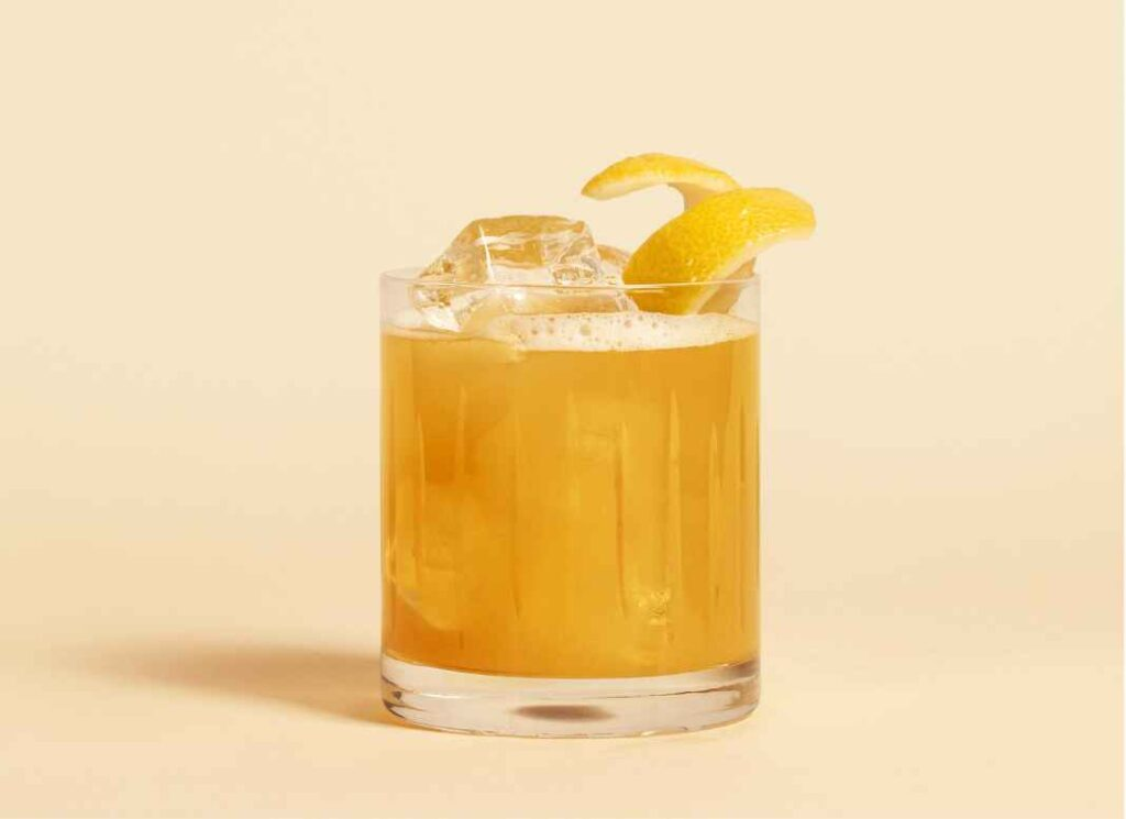 Bright orange cocktail in rocks glass garnished with yellow peel against pale yellow background.