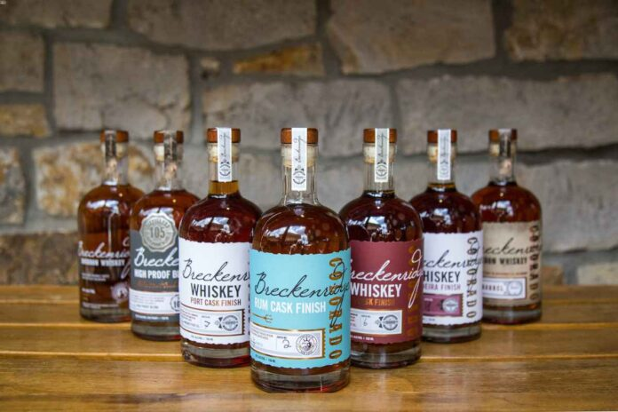Seven bottles of Breckenridge Distillery whiskey with different colored labels arranged in a