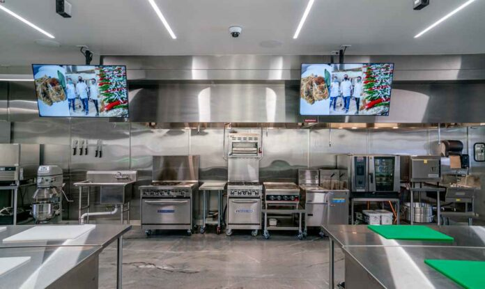 Professional culinary school kitchen with stainless steel tables, stovetops, ovens, sinks, and industrial mixers. Large screen tvs mounted on wall.